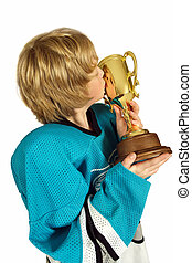 Kiss the cup - Young boy athlete kissing the championship...