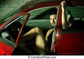 Man in car - Portrait of a sexy young man sitting in red car