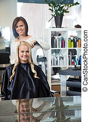 Woman Getting Her Hair Curled - Mirror reflection of stylist...