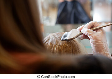 Hair Colour Application - Beautician applying hair color to...