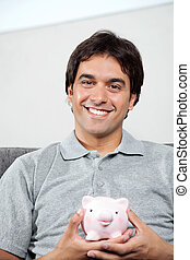 Happy Man Holding Piggybank - Portrait of young man in...