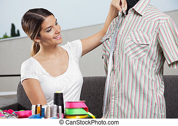 Woman Taking Shirt's Measurement - Young woman taking...