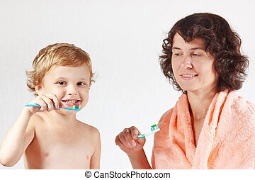 Mother teaches her little child to brush their teeth on a...