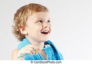 Little cute blond boy brushing his teeth on a white...