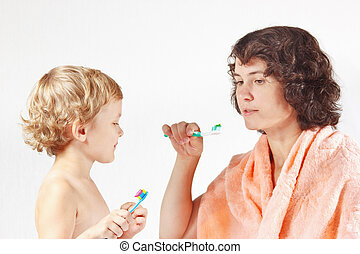 Young mother teaches her child to brush their teeth on a...