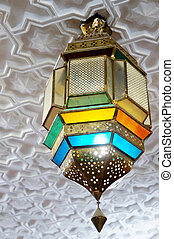 Arabic colorful lantern hanging from a white decorated...