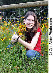 Arms around wildflowers - Attractive female teen kneels in a...