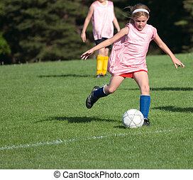 Soccer Player Kicking ball on field during practice