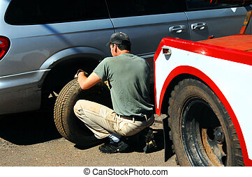 Auto tire repairman - Tire repairman replaces blown out tire...