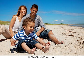 Family Enjoys Vacation on a Beach - Young family enjoys...