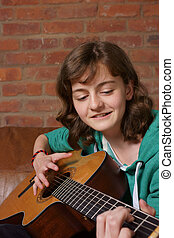 Teenage girl playing the guitar - A teenage girl playing an...