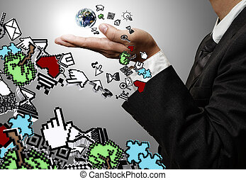 hand holds the earth and computer icons - business man hand...