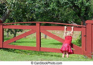 Little girl playing on a gate - Cute little girl in a red...