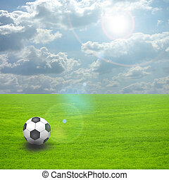 Soccer ball on the green field with sun set