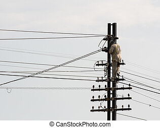 Electrician Man on electric poles. Repairs a Wire of the...