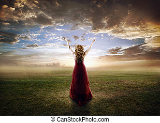 Woman praising - Woman lifting up her hands at sunset