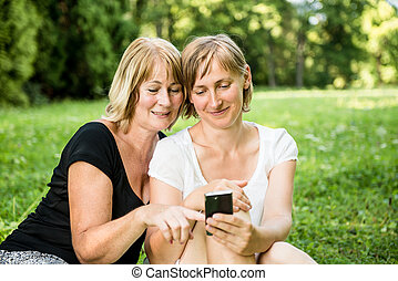 Senior mother and daughter with smartphone