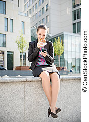 Business woman eating and working with phone - Smiling...