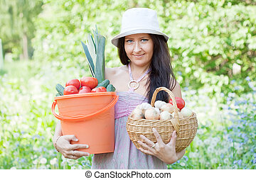 Happy woman holds vegetables harvest