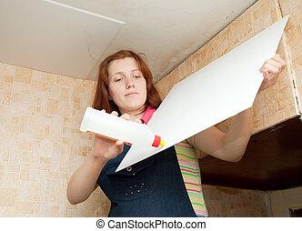 Girl glues ceiling tile   - Girl glues ceiling tile at home