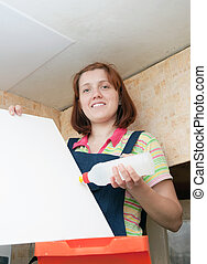 Woman glues ceiling tile - Woman glues ceiling tile at home...