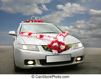 wedding car with tapes, florets and rings against the sky