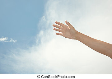Human hand on a summer sky background