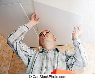 Man glues ceiling tile   - Man glues ceiling tile at home