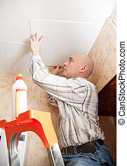Man glues ceiling tile at home