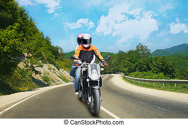 Two go on motorcycle on mountain road - biker and passenger...