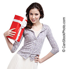 Young woman hands a Christmas gift wrapped in red paper, isolated on white