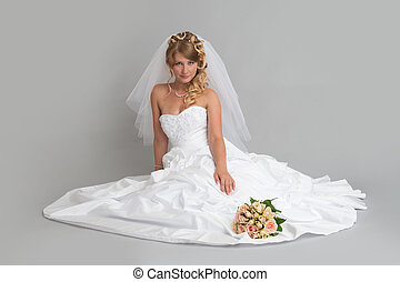 beautiful bride in a wedding dress sitting