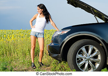 Woman in shorts with broken down car