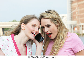 Two ladies listening to a mobile phone - Two ladies standing...