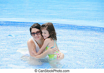 Mother and her baby having fun in the swimming pool.