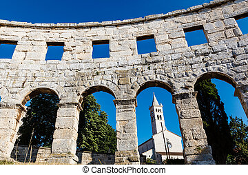 White Church Framed in the Arch of Ancient Roman...