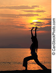 Sunset workout - A woman exercisingstretching at sunset by...
