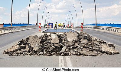 Roadworks - Damaged asphalt road and bridge in...