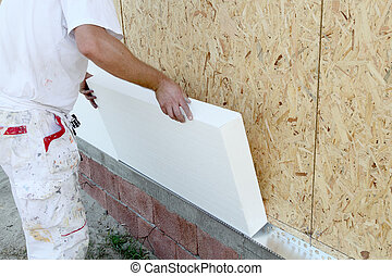 Insulation - Worker placing styrofoam sheet insulation to...