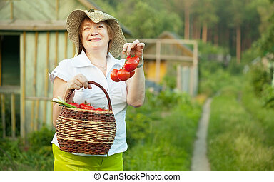 Happy mature woman with vegetables