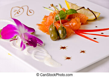 Smoked salmon appetizer plate, decorated with orchid.