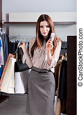 Girl with credit card is in the store