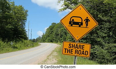 Share the road. - Share the road highway sign warns...