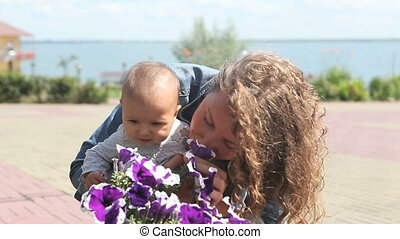 Smell flowers - Young mother holding her toddler and...