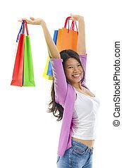 Happy shopper holding shopping bag high over white...