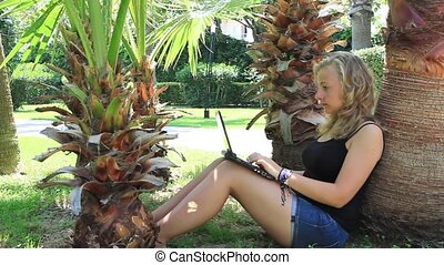 Woman working on laptop under a palm tree