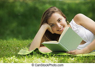 Smiling woman reading book - Closeup of a beautiful young...