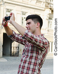 Smiling young man taking a photograph