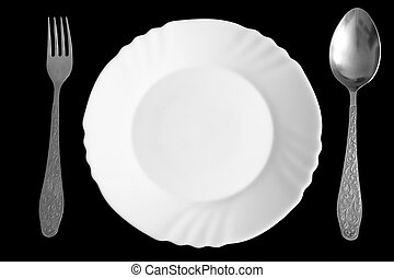 Plate, spoon and fork on a black background