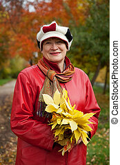 mature woman in autumn park - Portrait of mature woman in...